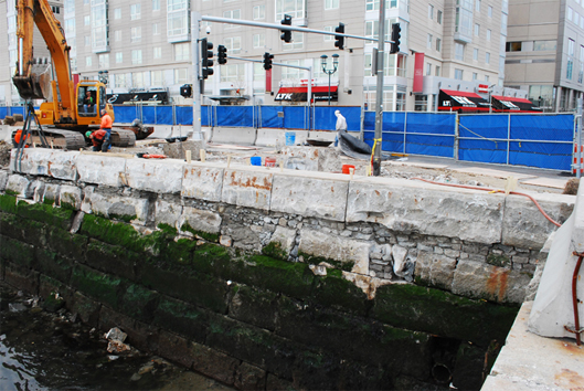 Re-laying the original sea wall's giant granit blocks